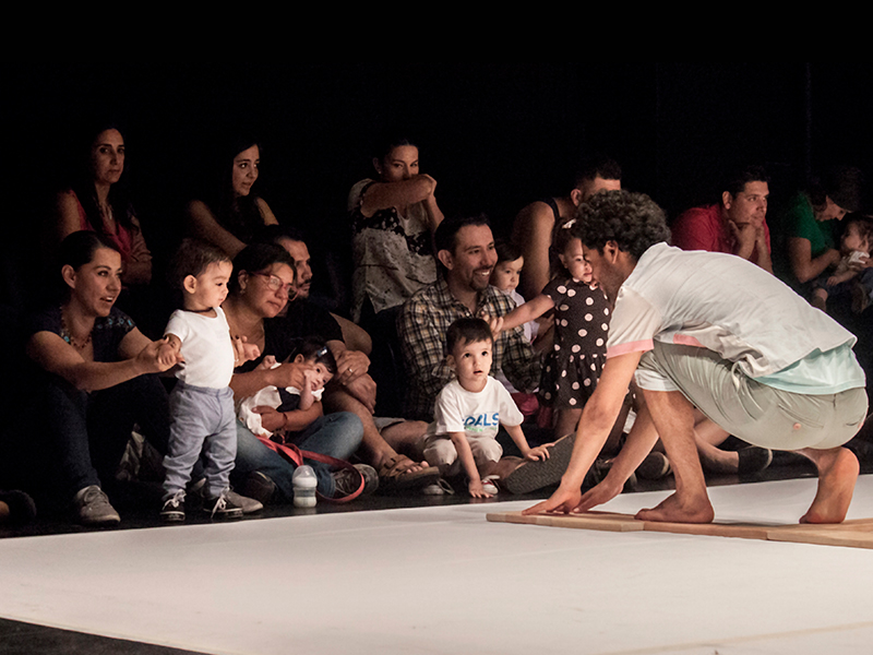 A man crawls on a piece of wood, staring into an audience of young children and families.