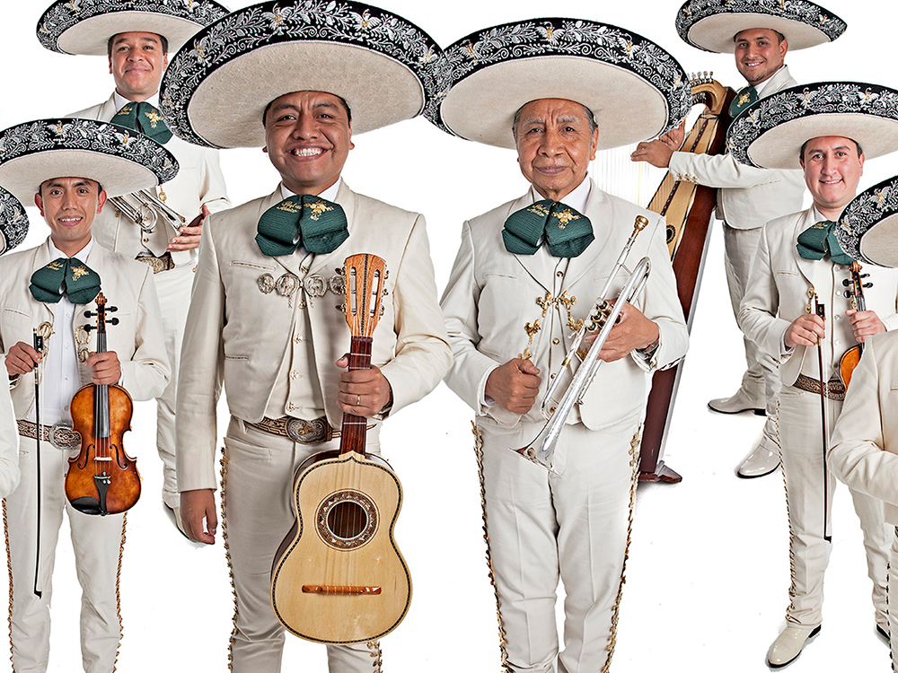 Six members of the group Mariachi Real de Mexico wearing traditional mariachi suits and hats and holding musical instruments